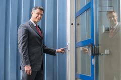 Mature Businessman Using Door Security System On Wall Stock Photos