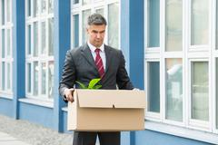 Sad Mature Businessman Carrying His Belongings In Box After Being Fired - stock photo