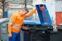 Working Man Looking In Dustbin On Street - stock photo