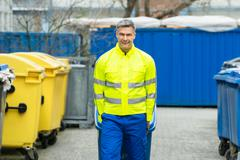 Happy Male Worker Walking With Dustbin On Street During Day - stock photo