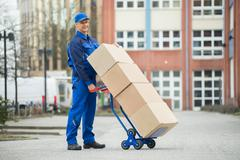 Mature Happy Deliveryman Holding Trolley Loaded With Cardboard Boxes On Stree Stock Photos
