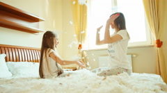 Happy daughter and mother sitting on the bed and playing Okay play in the fluff - stock footage