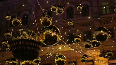 Shiny golden decorations hanging outdoors, sparkling to create festive mood Stock Footage