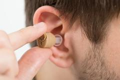 Close-up Of Young Man Wearing Hearing Aid In Ear - stock photo