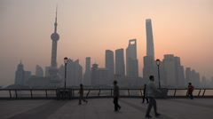 People do a morning walk on the Bund, Shanghai skyline, urban China Stock Footage