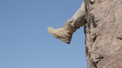 The man swung his legs off a cliff in army boots against the sky - stock footage
