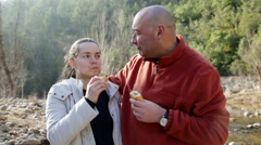 Handsome man and cheerful woman eating sandwitches at picnic outdoors Stock Footage