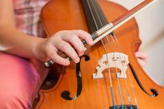 Cello instrument close up view, young musician playing - stock photo