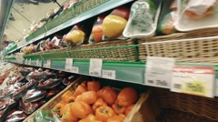 Tracking shot moving past fruit in a supermarket grocery.  Includes fruits and Stock Footage