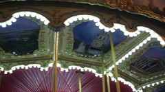 Illuminated merry-go-round rotating at amusement park, happy childhood memories - stock footage