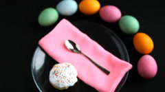 On black table lay different colored eggs, Easter cake, plate spoon, and napkin. Stock Footage