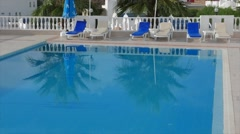 Deckchairs side of a swimming pool with palm trees reflection in the clear blue - stock footage