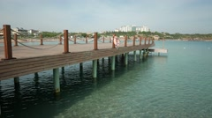 Emty wooden bathing pier with lifelines with beach and sea in a sunny day. 4k Stock Footage