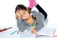 Little girl writing homework and having trouble doing it Stock Photos