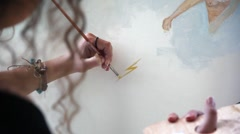 Woman artist painting with paintbrush next to sea - close up Stock Footage