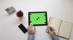 Man using tablet with a green background in the workplace Stock Footage