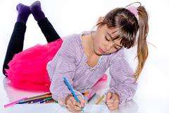 Beautiful eight year old girl drawing with color pencils - stock photo