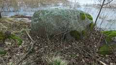 4K. Panoramic view of boulders with moss near frozen lake in early spring. - stock footage