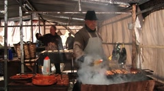 People cook meat and sausages at the street in Montblanc, Spain. Stock Footage