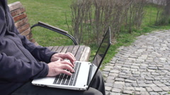 Casual businessman typing a document on laptop computer in city park Stock Footage