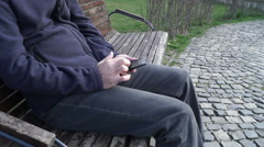 Casual man on citry park bench with mobile phone, sliding Stock Footage