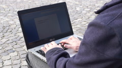 Woman typing a document on a tablet in city parc in a  March day Stock Footage