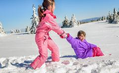 Little girl helping her friend to get up on the snow - stock photo