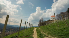 Capella In Slovenia With Moving Clouds and Grape-Vine In Foreground Stock Footage