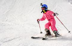 Little girl skiing fast downhill - stock photo