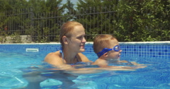 Mother and son in swimming pool. Son learning to swim Stock Footage