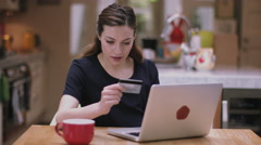 Young adult woman buying online using laptop in kitchen - stock footage