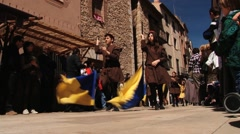 People walk with flags during Medieval festival in Montblanc, Spain. Stock Footage