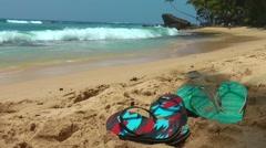 Flip Flops On Yellow Sandy Beach Near Sea Waves - stock footage