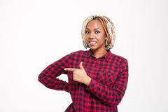 Smiling pretty young african american woman pointing away Stock Photos