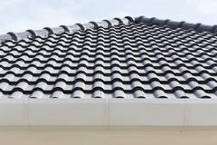 Stock Photo of white gutter on the roof top of house