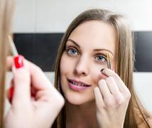 Shaping eyebrows with tweezer. Stock Photos