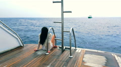 Beautiful girl relaxes on the stern of the yacht - stock footage