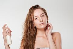 Young woman spraying hairspray - stock photo