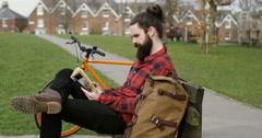 4k, A young man reading a book in a park as he takes a break from cycling. Stock Footage