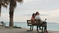 Two Young woman taking self portrait sitting on the seafront using smartphone Stock Footage