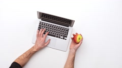 Man types on a laptop on his desk with apple.  Upview Stock Footage