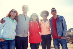 happy teenage friends in shades hugging on street - stock photo
