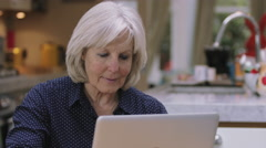 Senior woman buying online with credit card using laptop on kitchen table Stock Footage