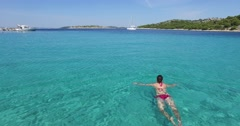 Woman swimming in clear, clean and brilliant, shimmering turquoise sea Stock Footage