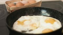 Common for a breakfast preparation of fried eggs on a cast-iron frying pan - stock footage