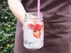 Hand on serving glass of iced strawberry soda drink Stock Photos