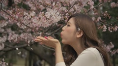 Beautiful Japanese girl smelling cheery blossom sakura blowing leafs Slowmo - stock footage