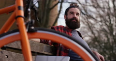 4k shot of a young man sitting on a bench while out for a cycle in the park. Stock Footage