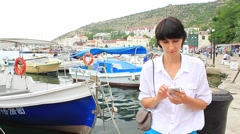 Young woman using cellphone on bay with motorboats Stock Footage