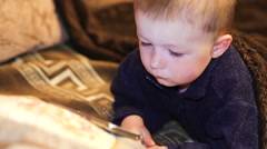 little boy watching cartoon on a smartphone indoor - stock footage